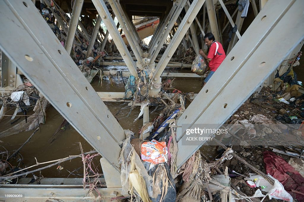 A scavenger collects valuable items under a bridge by the Ciliwung river following heavy floods in Jakarta on January 23, 2013. A spokesman for Indonesian National Disaster Mitigation Agency (BNPB) said more than 30,000 people were still living as refugees on January 22, while 20 people were killed during the widespread flooding that hit Jakarta last week. AFP PHOTO / ADEK BERRY