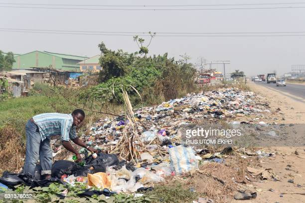 A scavenger picks leftover from a dump along Lagos Ibadan expressway on January 4 2017 Nigeria's President Muhammadu Buhari has decided to implement...