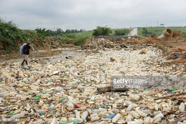 TOPSHOT A scavenger search for items amidst debris and plastic waste washed out from a river on May 23 2017 near the Ivorian capital Abidjan / AFP...