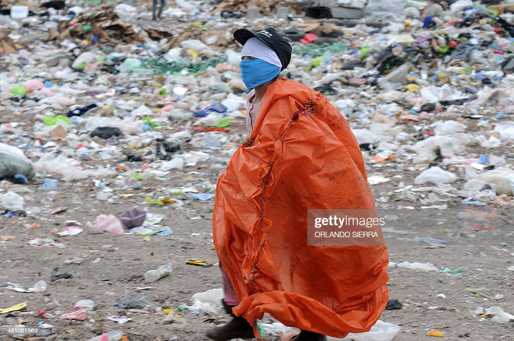 A scavenger walks amid the garbage at the municipal rubbish dump, 20 km north of Tegucigalpa, on November 21, 2013. Honduras, one of the poorest Latin American countries, will elect new president on November 24. AFP PHOTO / Orlando SIERRA.