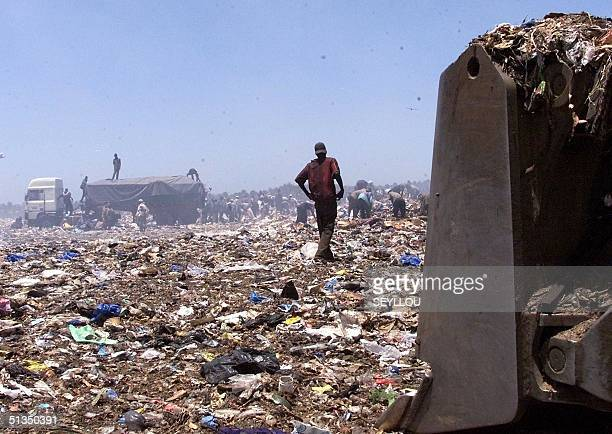 Scavengers congregate around a truck 10 April 2002 on the smoking rubbish tip of Mbeubeuss in a suburb of Dakar Hundreds make their living scavenging...