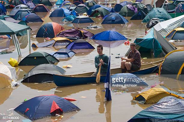 Scavengers in a Canadian canoe search the field of flooded tents at the very wet 2005 Glastonbury festival
