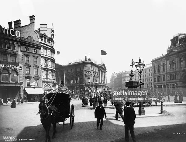 A scene at Piccadilly Circus in London with a horsedrawn hansom cab in the foreground