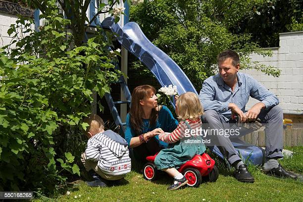 father mother and two children in the garden It's a warm spring day The father is sitting on a slide the little girl playing with her bobby and the...