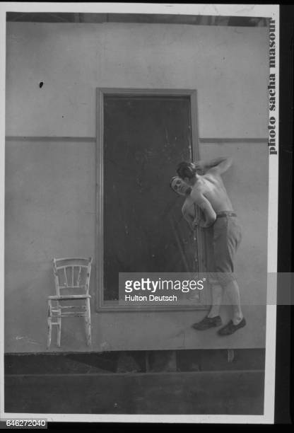 A scene from Jean Cocteau's play 'Le Sang d'un Poete' ca 1925 In an optical illusion a man with a bare torso looks into a tall mirror A chair with...