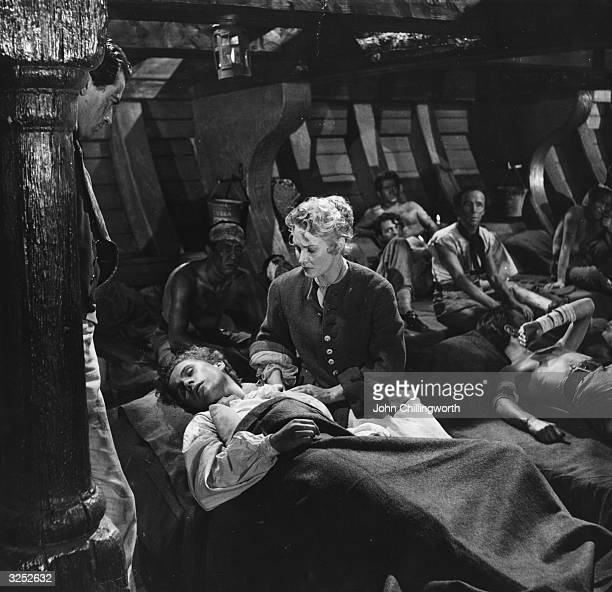 A scene from the film 'Captain Horatio Hornblower' based on the novel by C S Forester Lady Wellesley played by Virginia Mayo is tending the wounded...