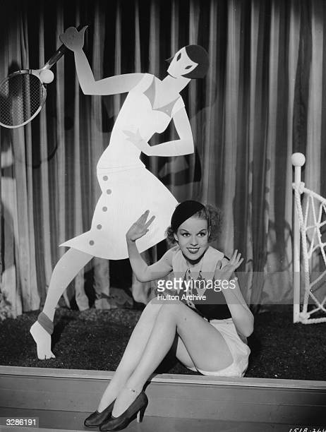 A scene from the film 'College Rhythm' in which an actress poses in front of a stylised cutout of a fashionable young coed in a tennis outfit The...