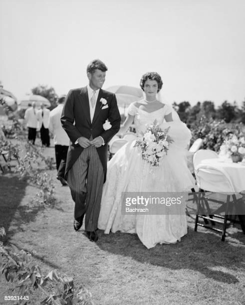 A scene from the KennedyBouvier wedding Groom John walks alongside his bride Jacqueline at an outdoor reception 1953 Newport Rhode Island
