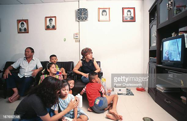 A scene from the living room of a privately owned house in a housing project in Bangkok Family members watch Television in the evening