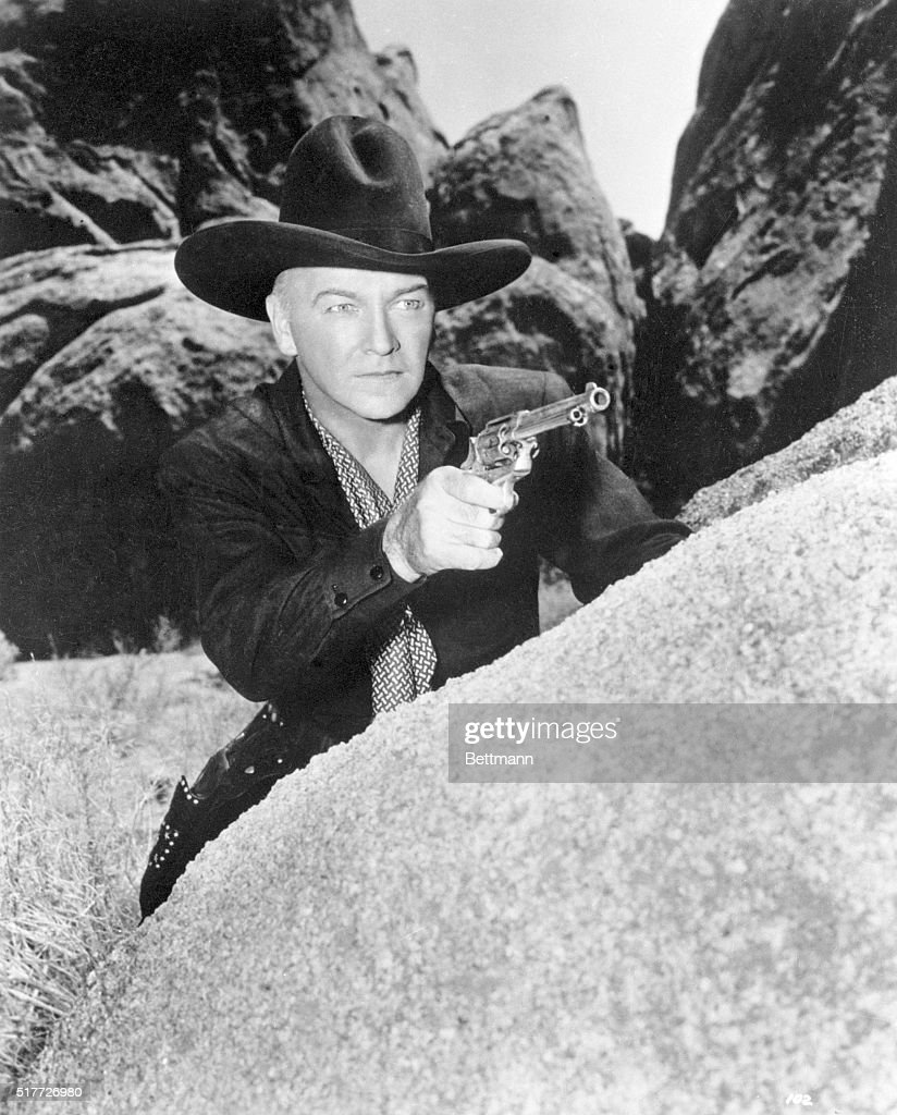 A scene from the television show Hopalong Cassidy, 1949-1952, in which Hopalong Cassidy draws his revolver and takes cover behind a large boulder.