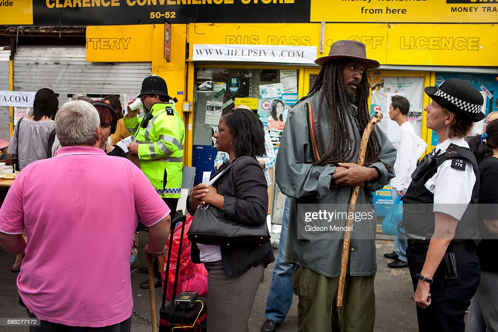 A scene of community policing as a policewoman talks to a local rasta priest outside Siva's shop during a community tea party held in Clarence Road...