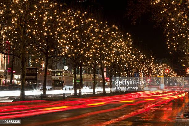 Scene with moving traffic and trees decorated with lights, Unter Den Linden, Berlin, Germany