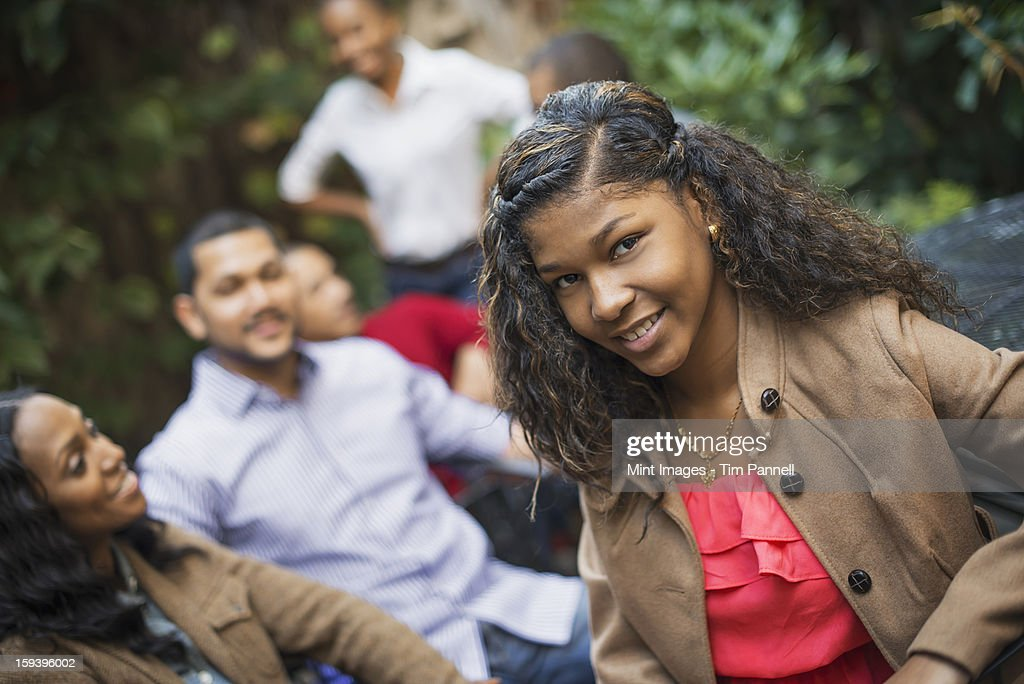 Scenes from urban life in New York City. A group of friends sitting together in a leafy square. man and woman. A teenage girl in the fore. : Stock Photo