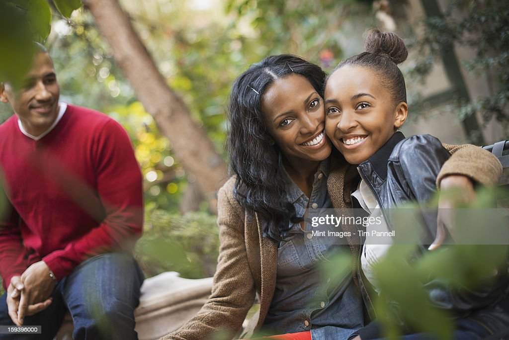 Scenes from urban life in New York City. Three people, two adults and a teenage girl. Mother and daughter hugging. : Stock Photo