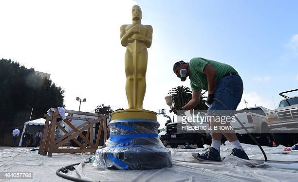 Scenic artist Rick Roberts touches up a statue of the Oscar with spray praint in a back lot off Hollywood Boulevard on February 21 as final...