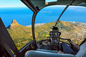 Helicopter cockpit flies in Lion's Head, coast and Cape Town in South Africa, with pilot arm and control board inside the cabin.