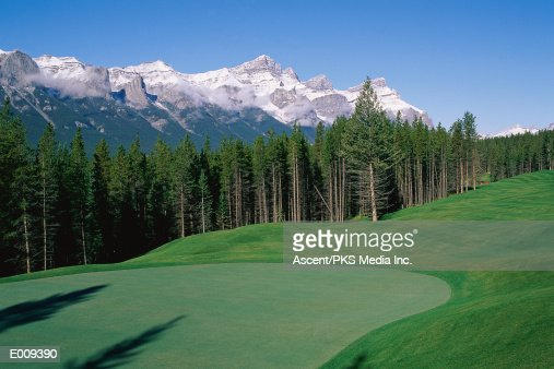 Scenic golf course with mountains in background : Stock Photo