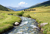 Beautiful field with a small river in swiss alpine valley near Davos. A church and houses on a background