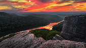A dramatic summer sunset reflects on the surface of the Big South Fork river as seen from a rocky outcrop in Kentucky.