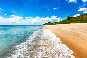 Sunny beach with golden sands blue sky and azure sea