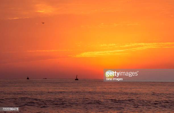 Scenic sunset over Yellow Sea with boats in background