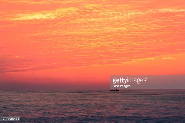 Scenic sunset over Yellow Sea with fishing boat in background