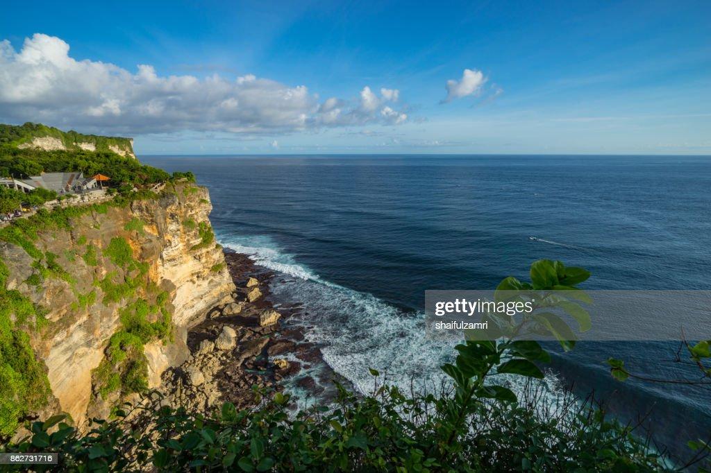 A scenic Uluwatu cliff with pavilion and blue sea in Bali, Indonesia. : Stock Photo