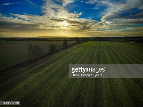 Scenic View Of Agricultural Field Against Sky At Sunset