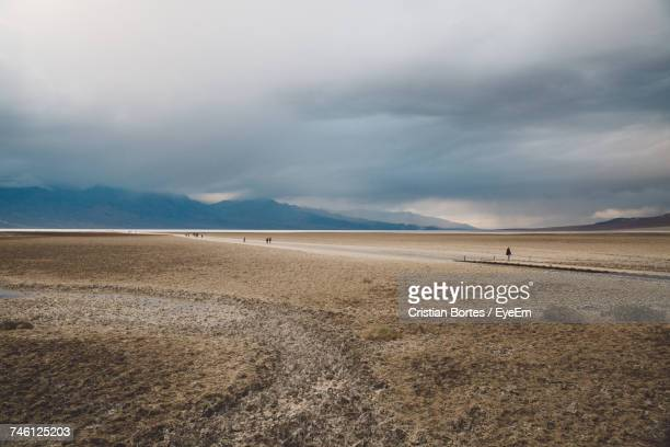 Scenic View Of Arid Landscape Against Cloudy Sky