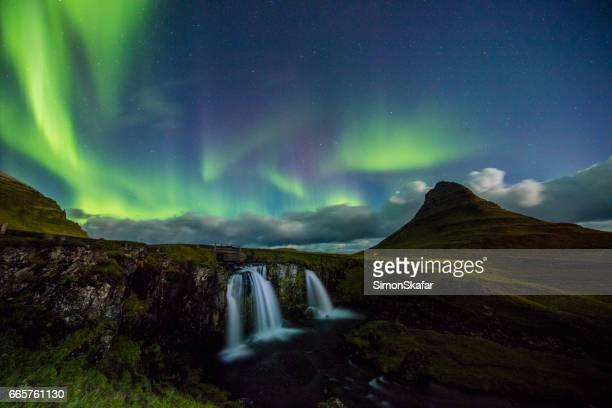 Scenic view of Aurora Borealis over waterfall