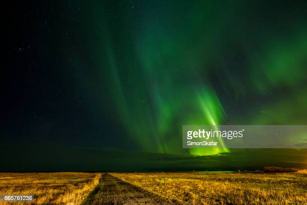 Scenic view of aurora over dirt road and landscape