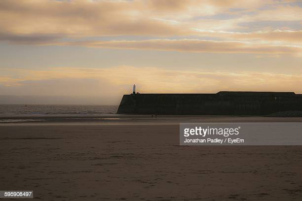 Scenic View Of Beach Against Cloudy Sky At Porthcawl During Dusk