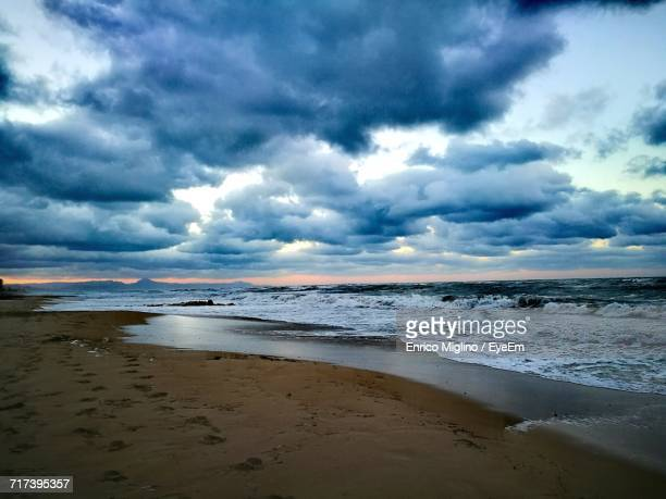 Scenic View Of Beach Against Dramatic Sky