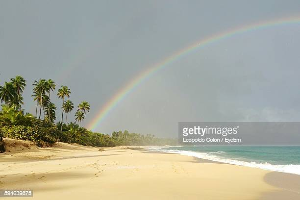 Scenic View Of Beach And Sea Against Sky With Rainbow