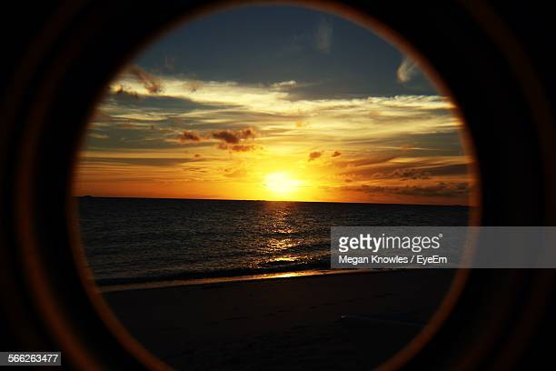 Scenic View Of Beach At Sunset Through Window