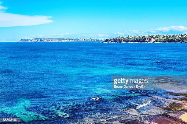 Scenic View Of Blue Sea Against Sky On Sunny Day
