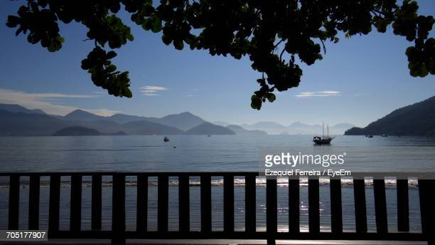 Scenic View Of Calm Sea Against Mountain Range