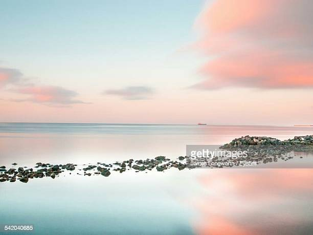 Scenic View Of Calm Sea Against Sky During Sunrise