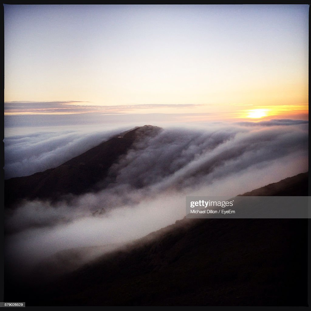 Scenic View Of Cloud Covered Mountains At Morning