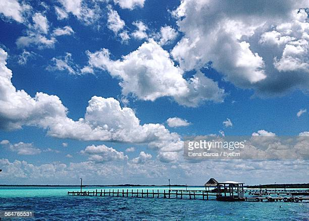 Scenic View Of Cloudy Sky Over Pier In Sea