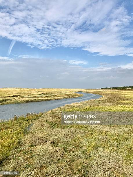 Scenic View Of Countryside Landscape Against Cloudy Sky