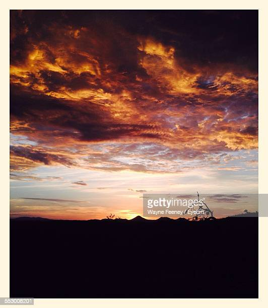 Scenic View Of Dramatic Sky Over Silhouetted Landscape During Sunset