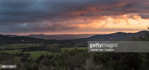 Scenic View Of Field Against Dramatic Sky At Sunset