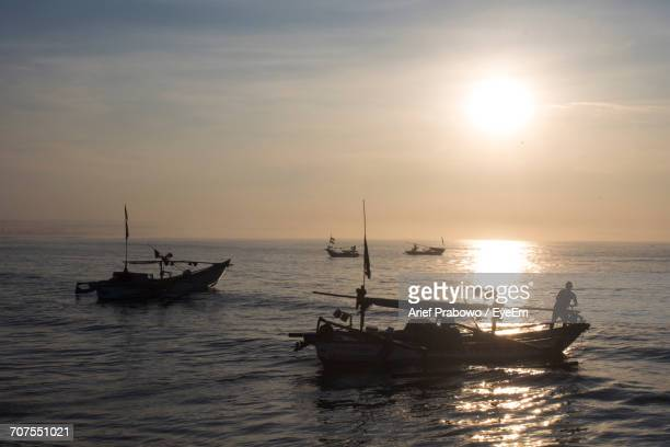 Scenic View Of Fishing Boats During Sunrise