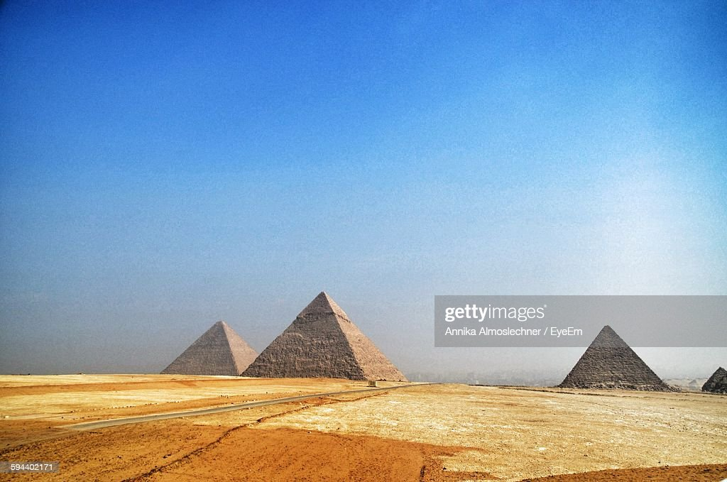 Scenic View Of Giza Pyramids On Desert Against Clear Sky