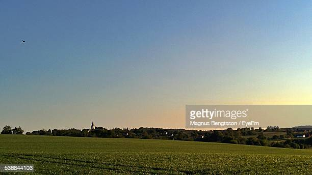 Scenic View Of Grassy Field Against Clear Sky At Sunset
