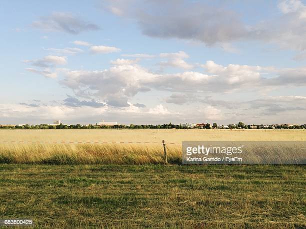 Scenic View Of Grassy Field Against Cloudy Sky On Sunny Day
