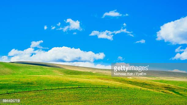 Scenic View Of Grassy Landscape Against Blue Sky