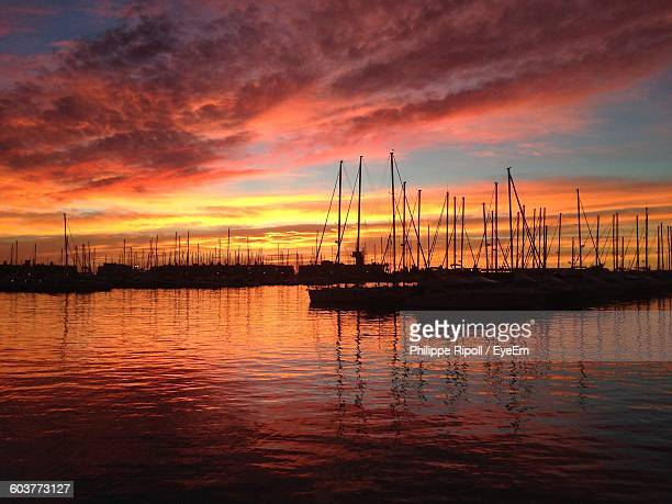 Scenic View Of Harbor On Sea Against Sky During Sunset