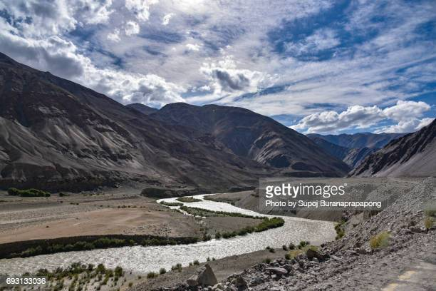 Scenic view of high mountain road in rugged rock against the background of dramatic blue sky, Leh district, Ladakh range, Himalayas, Jammu & Kashmir, Northern India